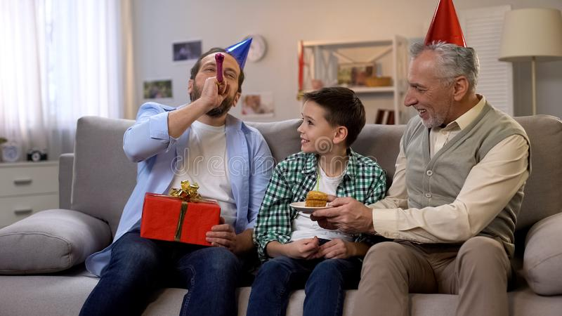 Father with party blower and grandfather congratulating little son with birthday royalty free stock image
