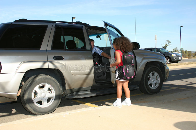 Father picking up girl in SUV. A view of a father opening the door of an SUV as he picks up his school aged daughter after school stock image