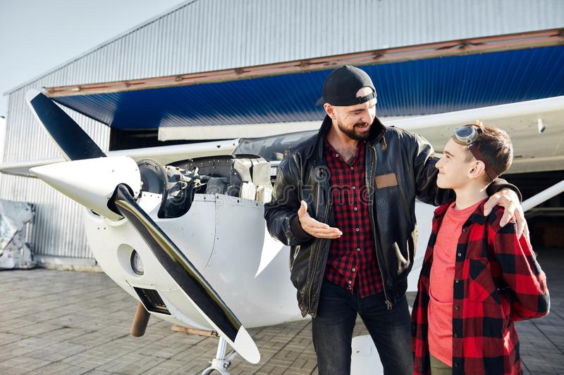 Father in pilot jacket stands with his son near light airplane royalty free stock photo