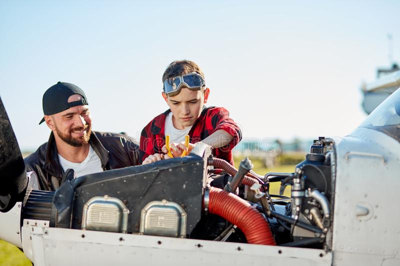 Father pilot teaching son to do repair works, explains arrangement of gear royalty free stock images