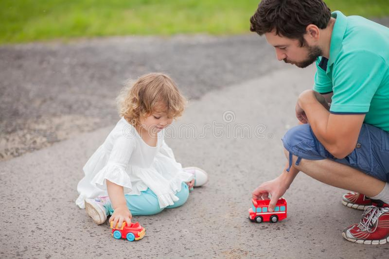 Little girl playing with toy cars with her father. Father play with his toddler daughter in boys games. Two color cars. Family leisure. Loving caring single stock photos