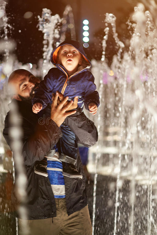 Father play with kid in fountain stock photos