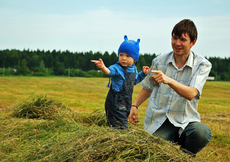 Father play with son on field stock images