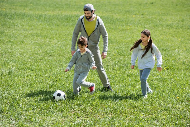 father playing football with children on grass stock photography