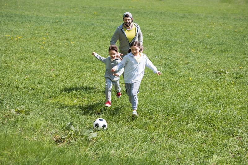 father playing football with daughter and son stock photography