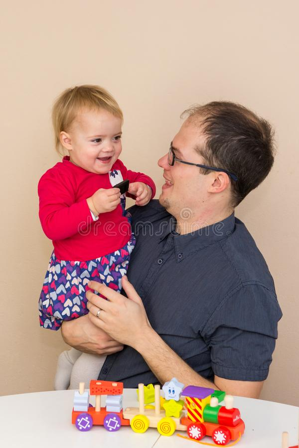 Father playing with her daughter with wooden toys. stock image