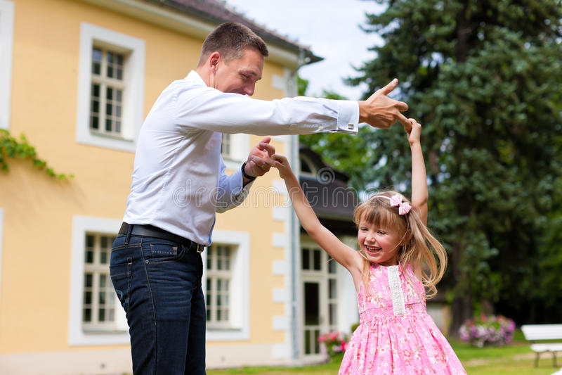 Father is playing with his daughter on a meadow stock photography