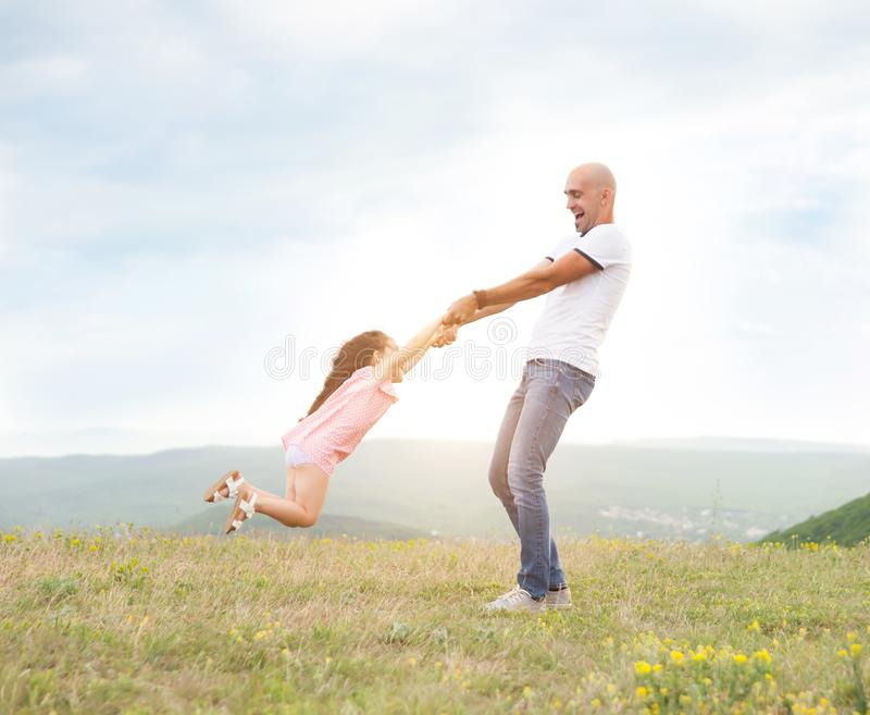 Father playing with his daughter in sunny field royalty free stock photo