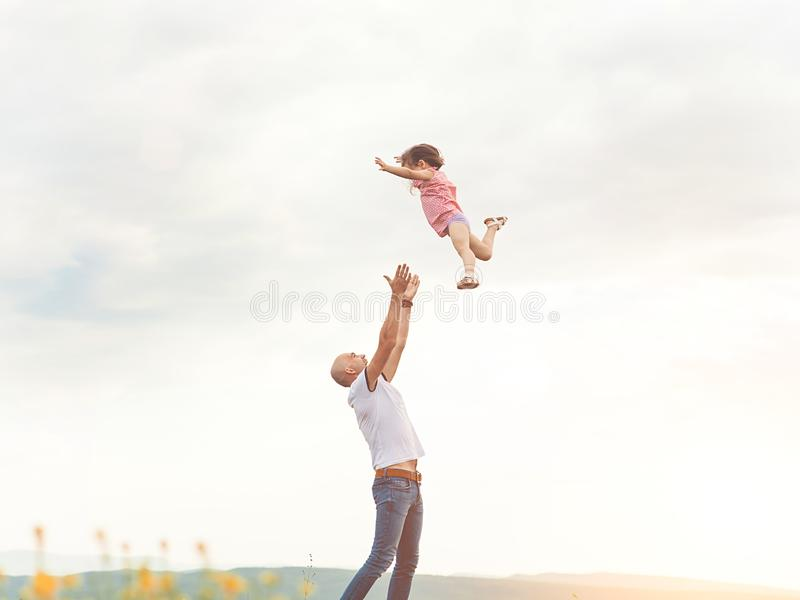 Father playing with his daughter in sunny field stock images