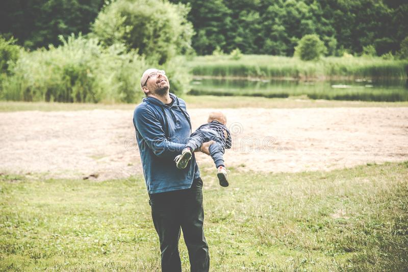father playing with his kid outdoors, flying stock photography