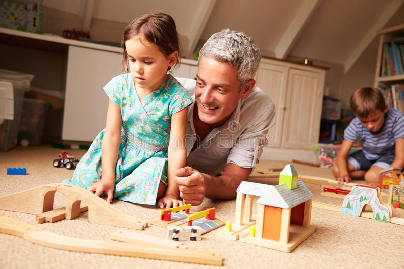 Father playing with kids and toys in an attic playroom stock photography