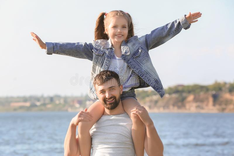 Father playing with little daughter near river on sunny day stock photography