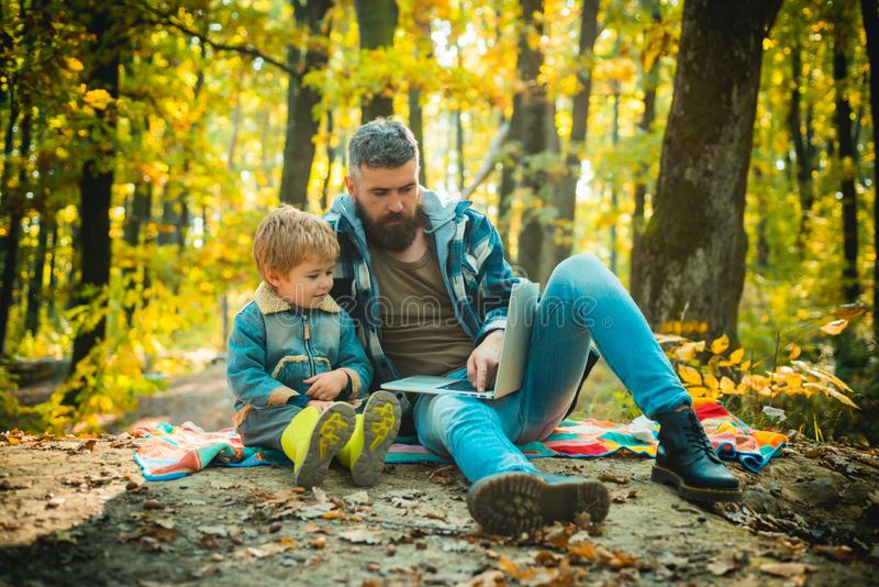 Father playing with little son on a picnic in the park in early autumn day. Cute little boy with his father during stock images