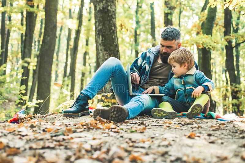 Father playing with little son on a picnic in the park in early autumn day. Parent teach baby. Cute little boy with his. Father during stroll in the forest stock images