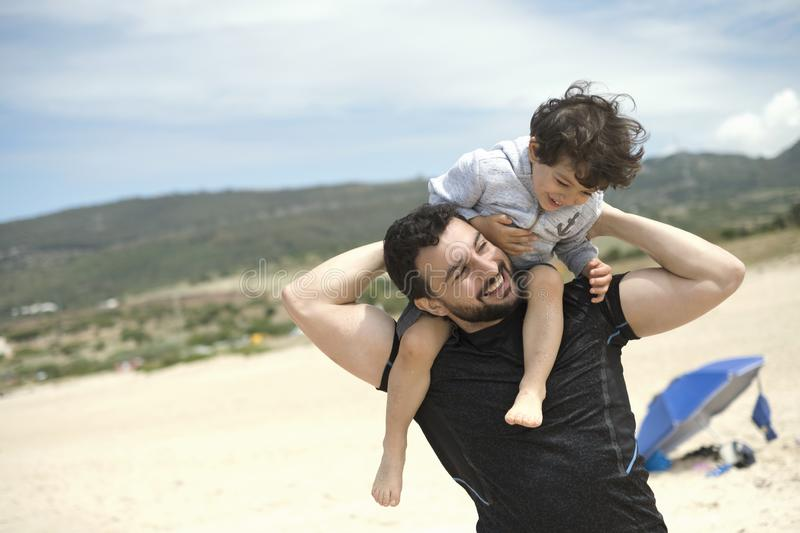 Father playing with son in Bolonia beach royalty free stock image