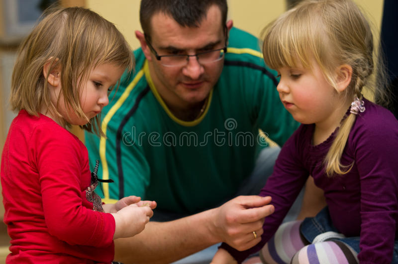 Father playing with children. Father playing with two young preschool daughters stock image