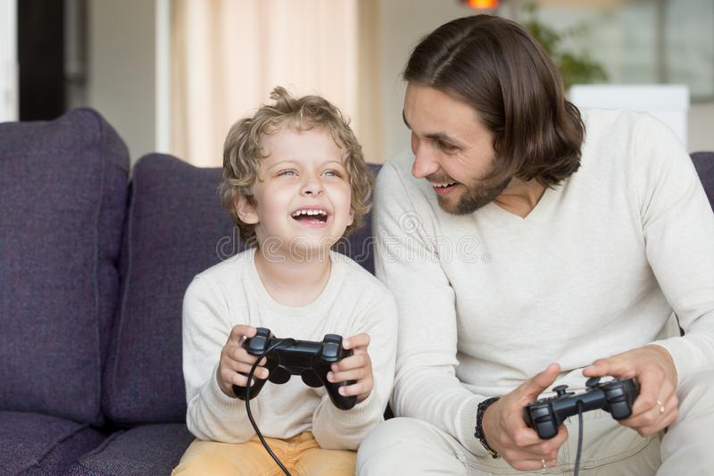 Father playing video games with son having fun holding controlle stock photo