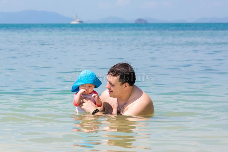Father plays with his daughter in the water at sea. The baby girl is teething stock photo
