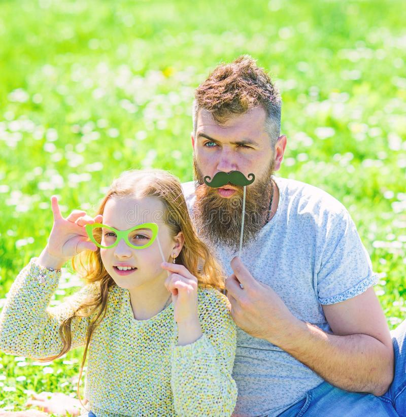 Father posing with mustache and child posing with eyeglasses photo booth attribute. Dad and daughter sits on grassplot. Grass on background. Detectives concept stock image