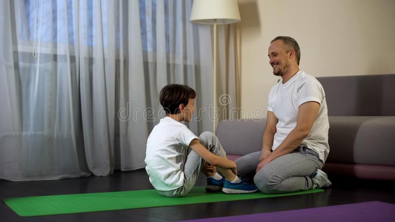 Father praising and supporting son after training, exercising at home, sport stock image