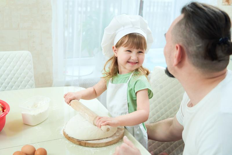 Father preparing food with my daughter. a man teaches a child to cook. the process of cooking in a bright kitchen. home cooking is. Father preparing food with my royalty free stock photo