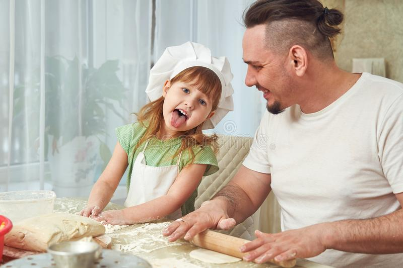 Father preparing food with my daughter. a man teaches a child to cook. the process of cooking in a bright kitchen. home cooking is royalty free stock photos