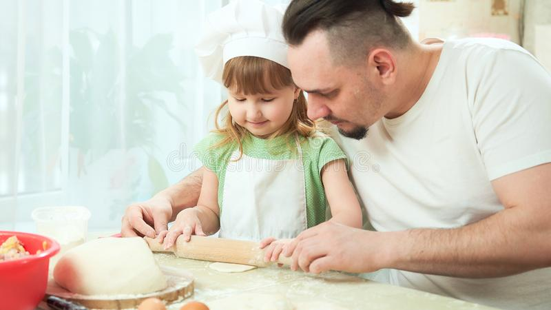 Father preparing food with my daughter. a man teaches a child to cook. the process of cooking in a bright kitchen. home cooking is. Father preparing food with my stock images