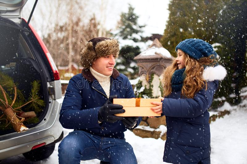 Father presents daughter a gift box on snowy winter day outdoors. Christmas tree in large trunk of family car. Girl royalty free stock image
