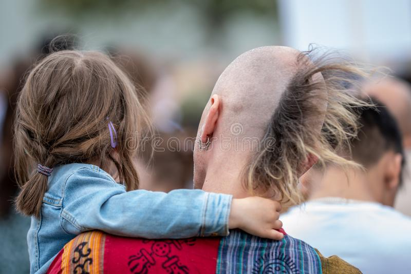 Father with punk rocker hair cut carrying his daughter in his arms royalty free stock photos