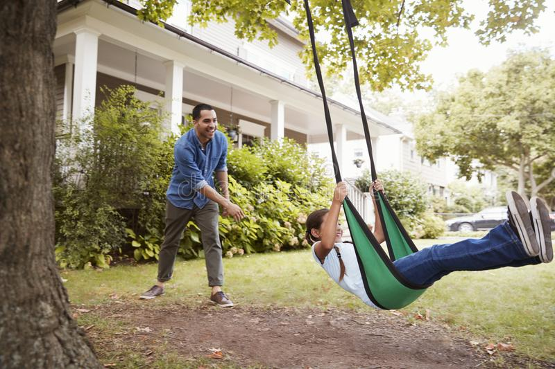Father Pushing Daughter On Garden Swing At Home stock photos
