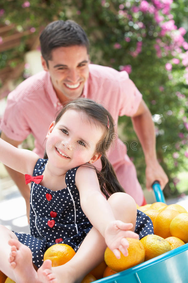 Download Father Pushing Daughter In Wheelbarrow Stock Photo - Image of barrow, child: 27273114