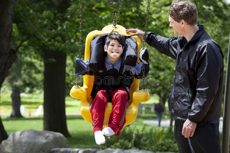 Father pushing disabled boy in special needs swing royalty free stock photo