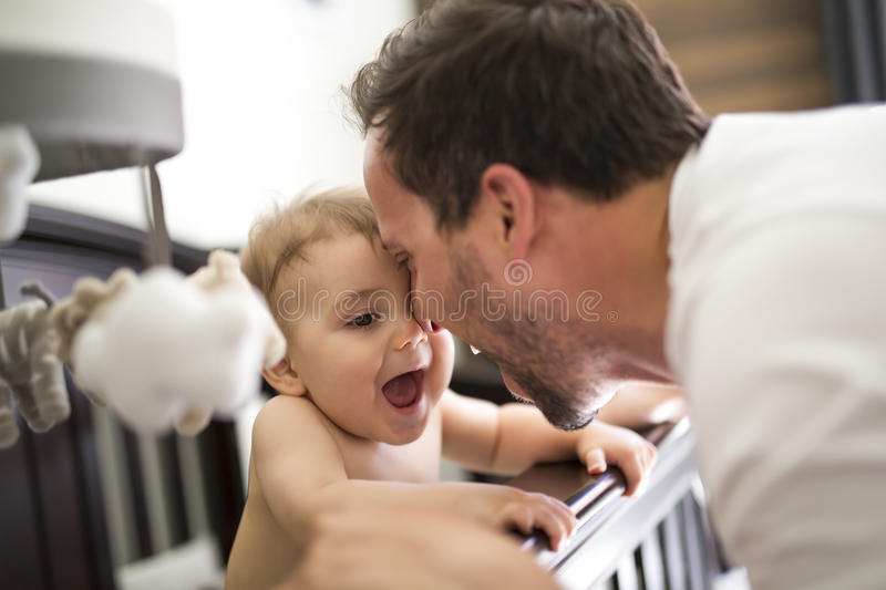 Father putting baby to sleep at the crib. A father putting baby to sleep at the crib royalty free stock photos