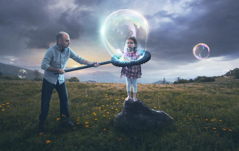 Father putting child in a bubble. A father puts his reluctant child inside a bubble stock photos