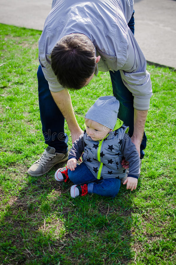 Father raises his son who fell making first steps stock image