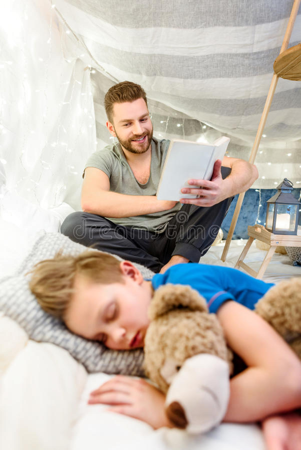 Father reading book to cute little boy sleeping with teddy bear stock image
