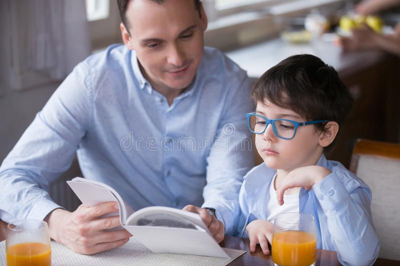 Father reading a book to little son stock photo