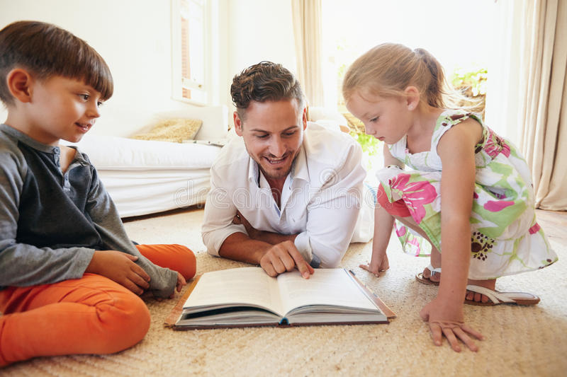Father reading stories to his children stock images