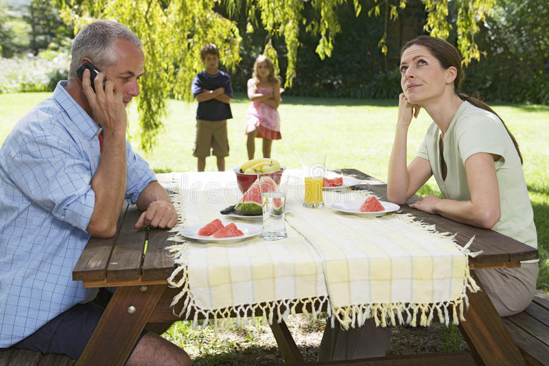 A father receiving a business call during a family lunch in the garden royalty free stock photography