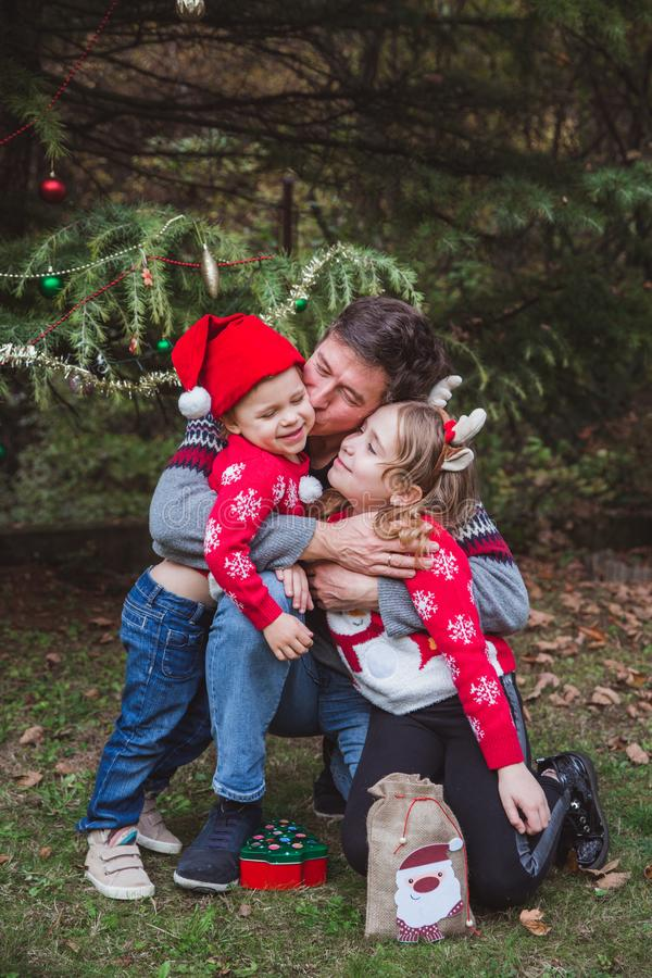 Father in red Christmas hat and two daughters in red sweaters happy near Christmas tree outdoor in the yard of the house royalty free stock photos