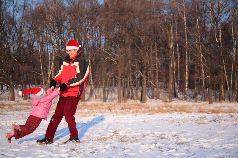 Father rotate daughter in winter stock photo