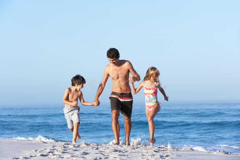 Father Running With Children Along Sandy Beach royalty free stock photography