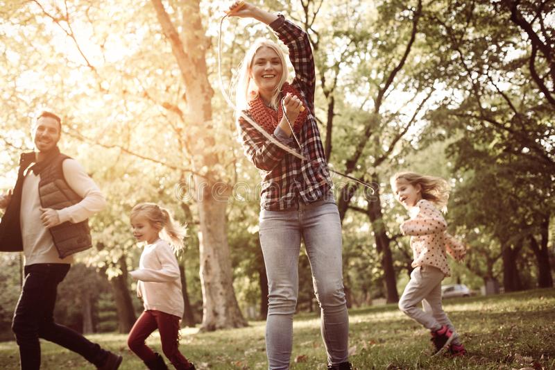 Father running with daughters trough park mother holding jum stock images