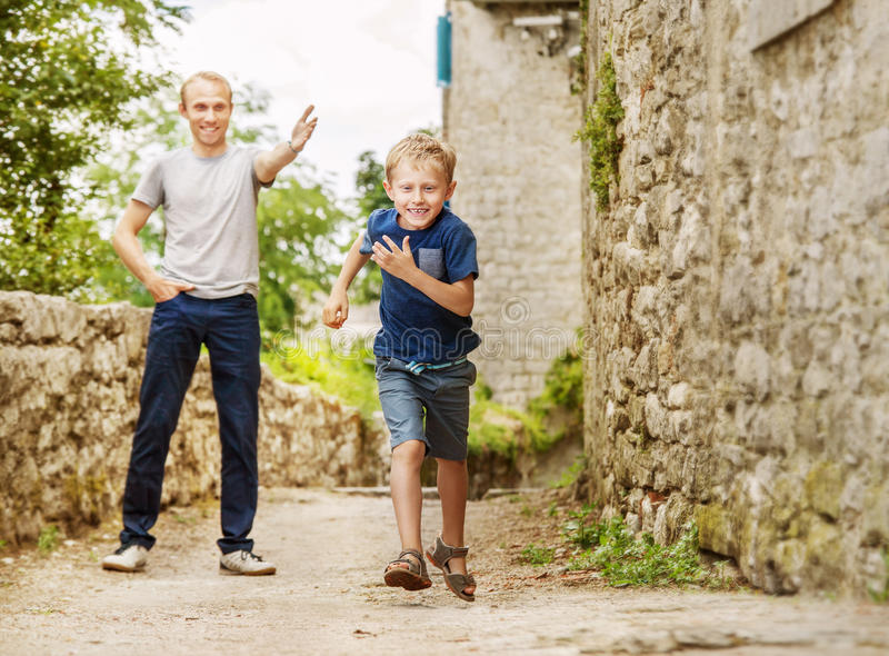 Father and running son on old street stock photos