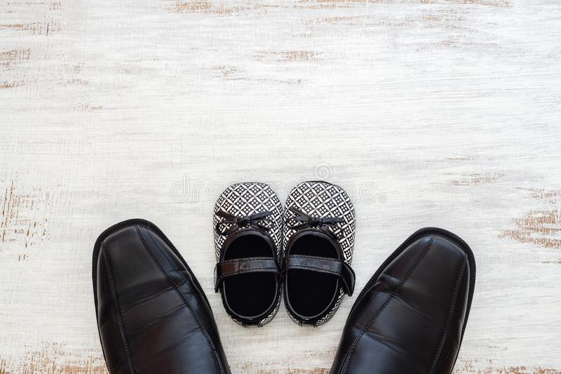 Fathers business black shoes and daughter baby black shoes on rustic white wood background. Concept of family, single parent stock photography