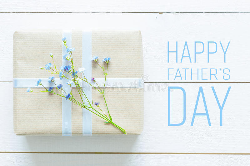Father`s day background. White wooden table with blue flowers and a present, father`s day concept royalty free stock photo