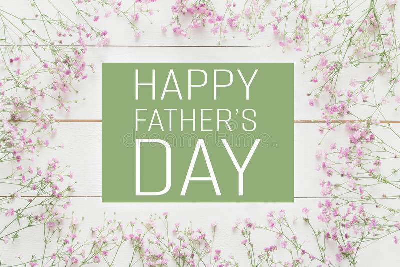 Father`s day background. White wooden table with pink flowers
