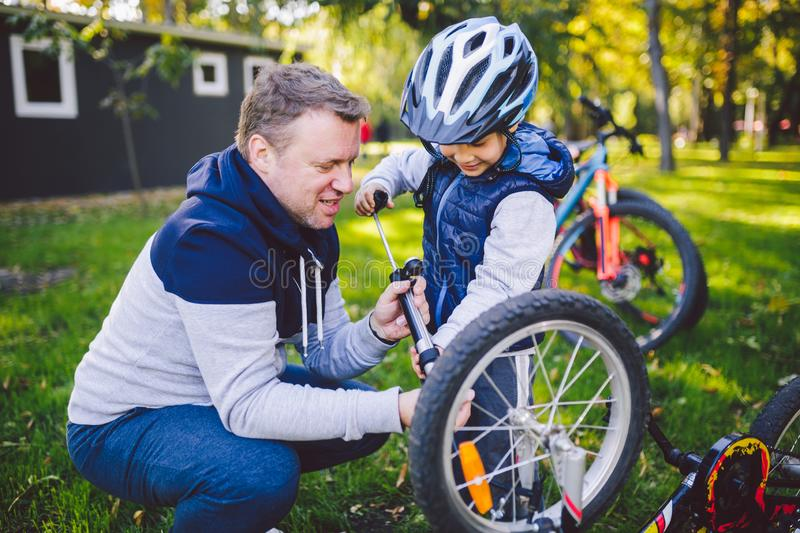 Father`s day Caucasian dad and 5 year old son in the backyard near the house on the green grass on the lawn repairing a bicycle, stock photo