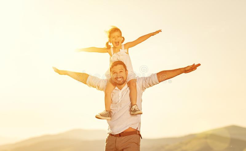 Father`s day. child daughter sits on her dad shoulders outdoors. On a summer beach royalty free stock photos