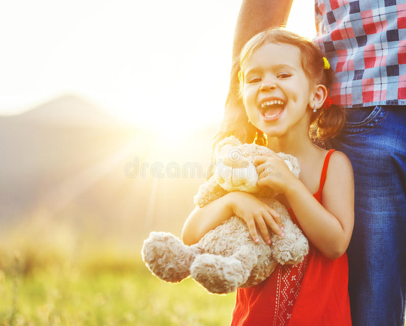 Father`s day. Child girl hugging father in nature at sunset. In summer royalty free stock image